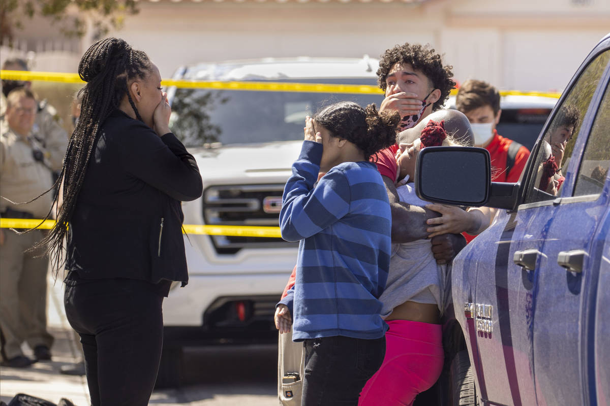 Family members console each other near where the Clark County Fire Department works a house fir ...