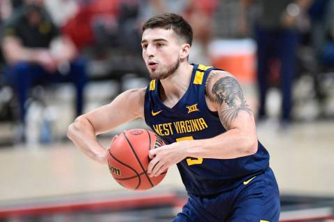 West Virginia's Jordan McCabe (5) passes the ball during the first half of an NCAA college bask ...