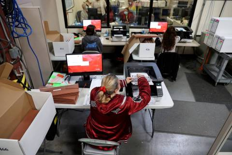 County Election Department staff work on the recount in the Commission District C race between ...