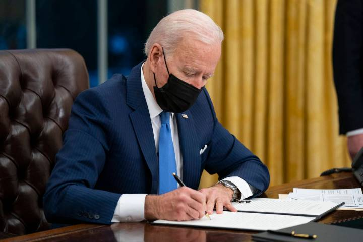 President Joe Biden signs an executive order on immigration. (AP Photo/Evan Vucci, File)