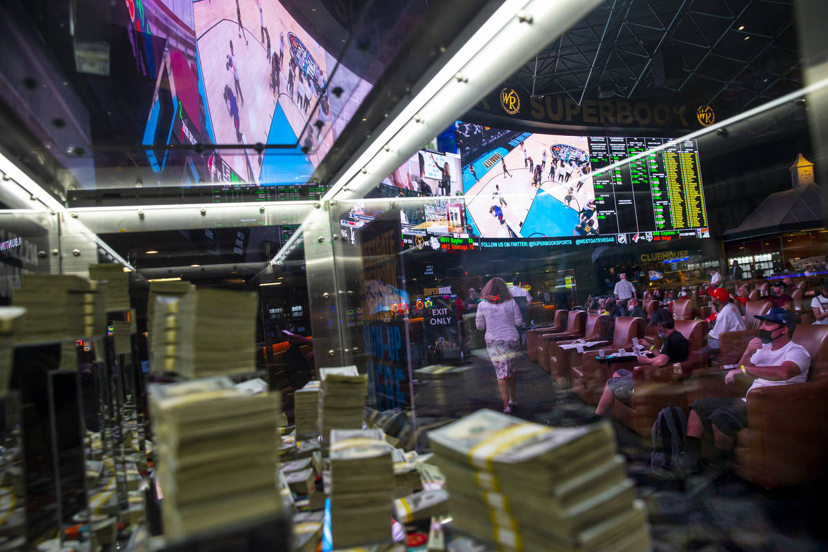 Basketball fans walk to the Westgate sportsbook windows to collect winnings after Baylor defeat ...