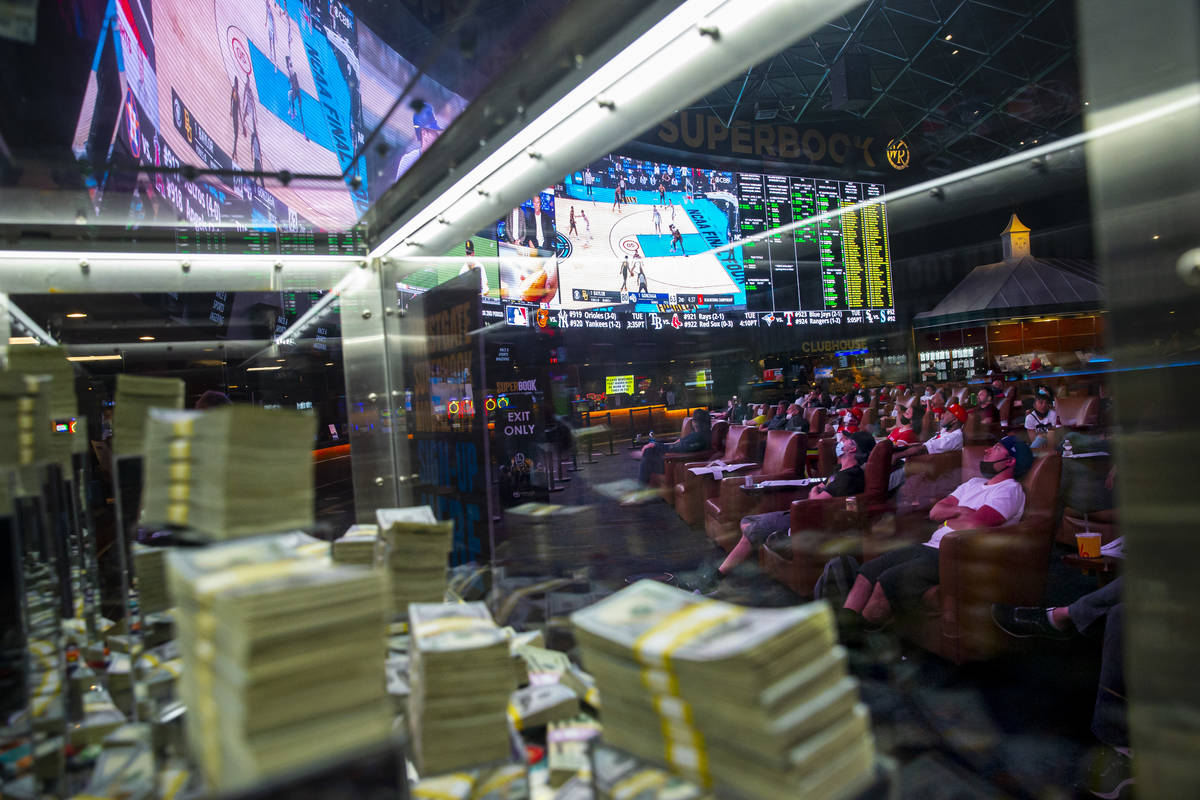 Basketball fans, framed through a promotional cash display, watch the NCAA championship basketb ...