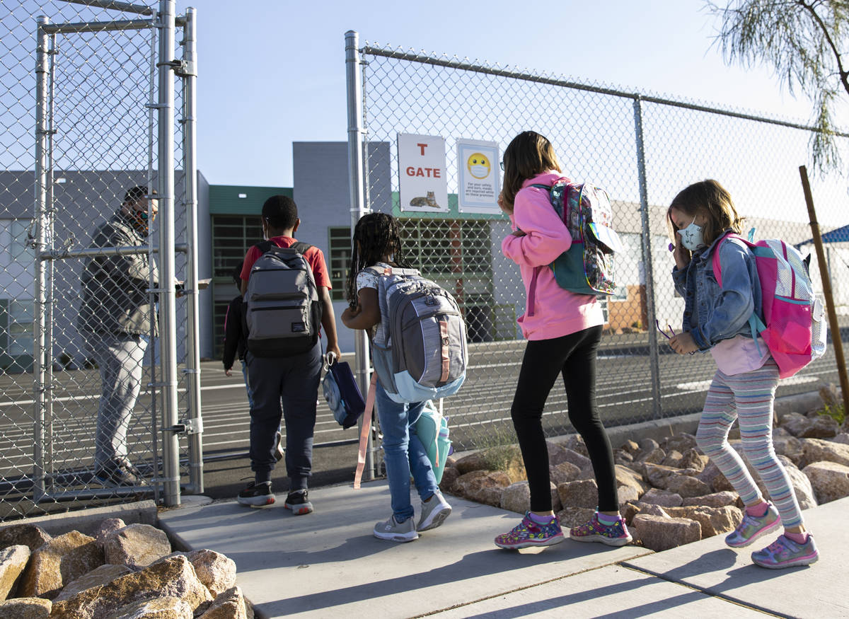 Evan Billings, left, a music teacher at Tyrone Thompson Elementary School, checks in students a ...