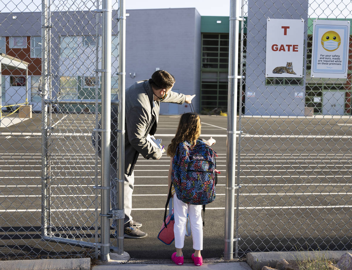 Evan Billings, a music teacher at Tyrone Thompson Elementary School, directs a student as she a ...