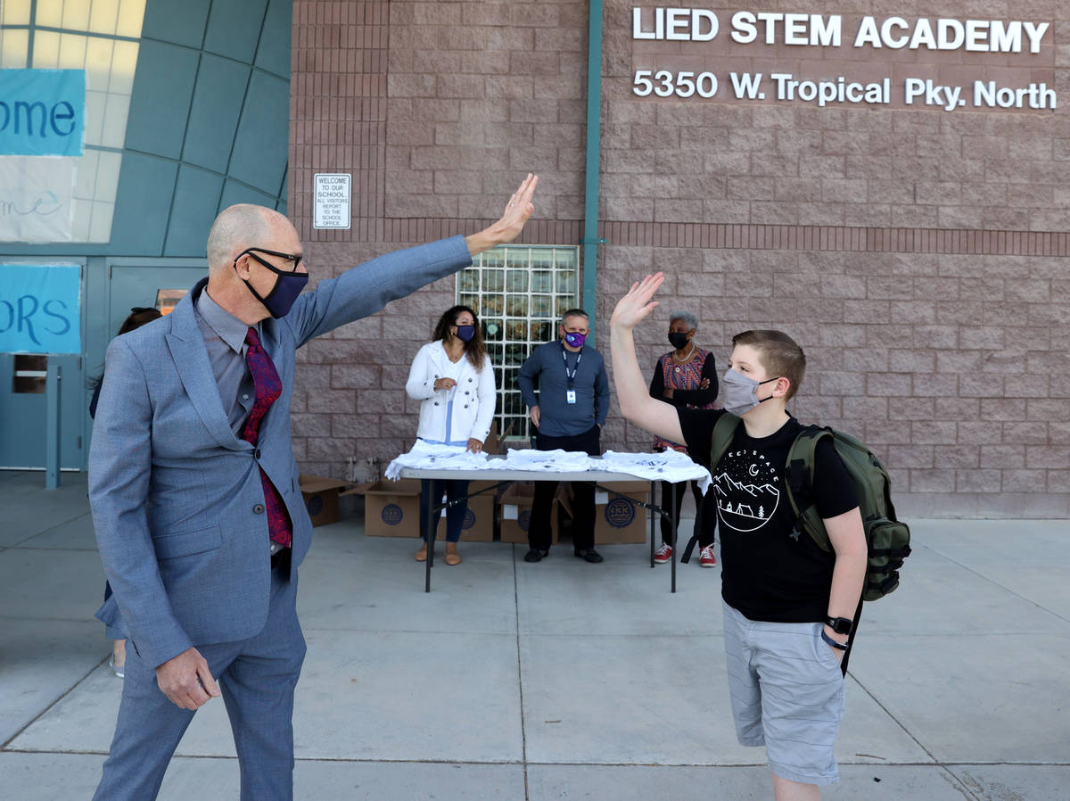 Principal Derek Fialkiewicz gives a virtual high-five to seventh grader Aaiden Bezemer, 12, on ...