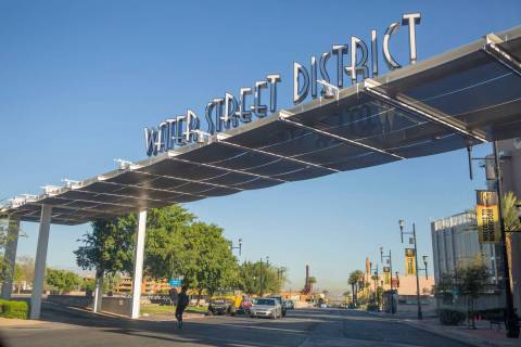 A pedestrian crosses underneath a sign identifying the iconic Water Street District on South Wa ...