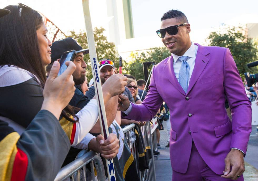 Golden Knights' Ryan Reaves signs autographs on the gold carpet after arriving for the NHL seas ...