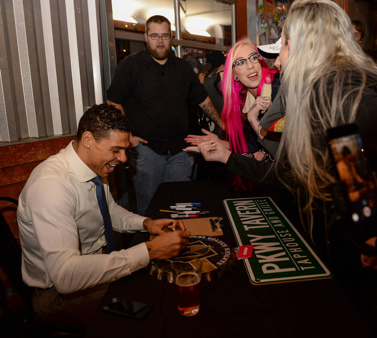 Vegas Golden Knights player Ryan Reaves signs memorabilia for fans at a party for the release o ...
