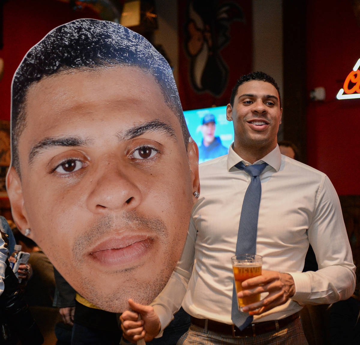 Vegas Golden Knights player Ryan Reaves holds up a cutout of himself at a party for the release ...