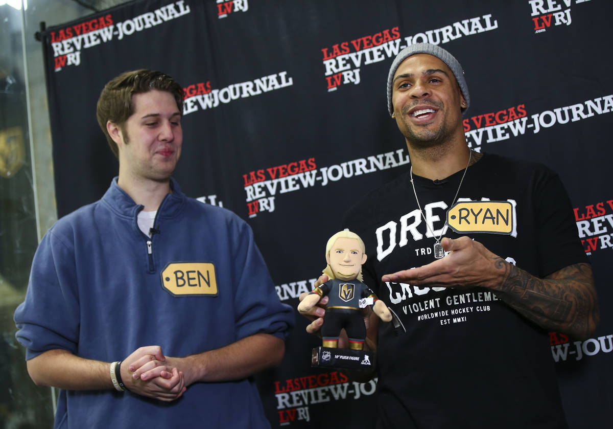 Golden Knights forward Ryan Reaves, right, holds a William Karlsson doll while participating in ...