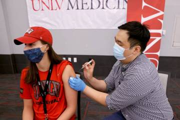 UNLV volleyball player Kate Brennan, 20, gets a COVID-19 vaccination from Andrew Choi at the UN ...