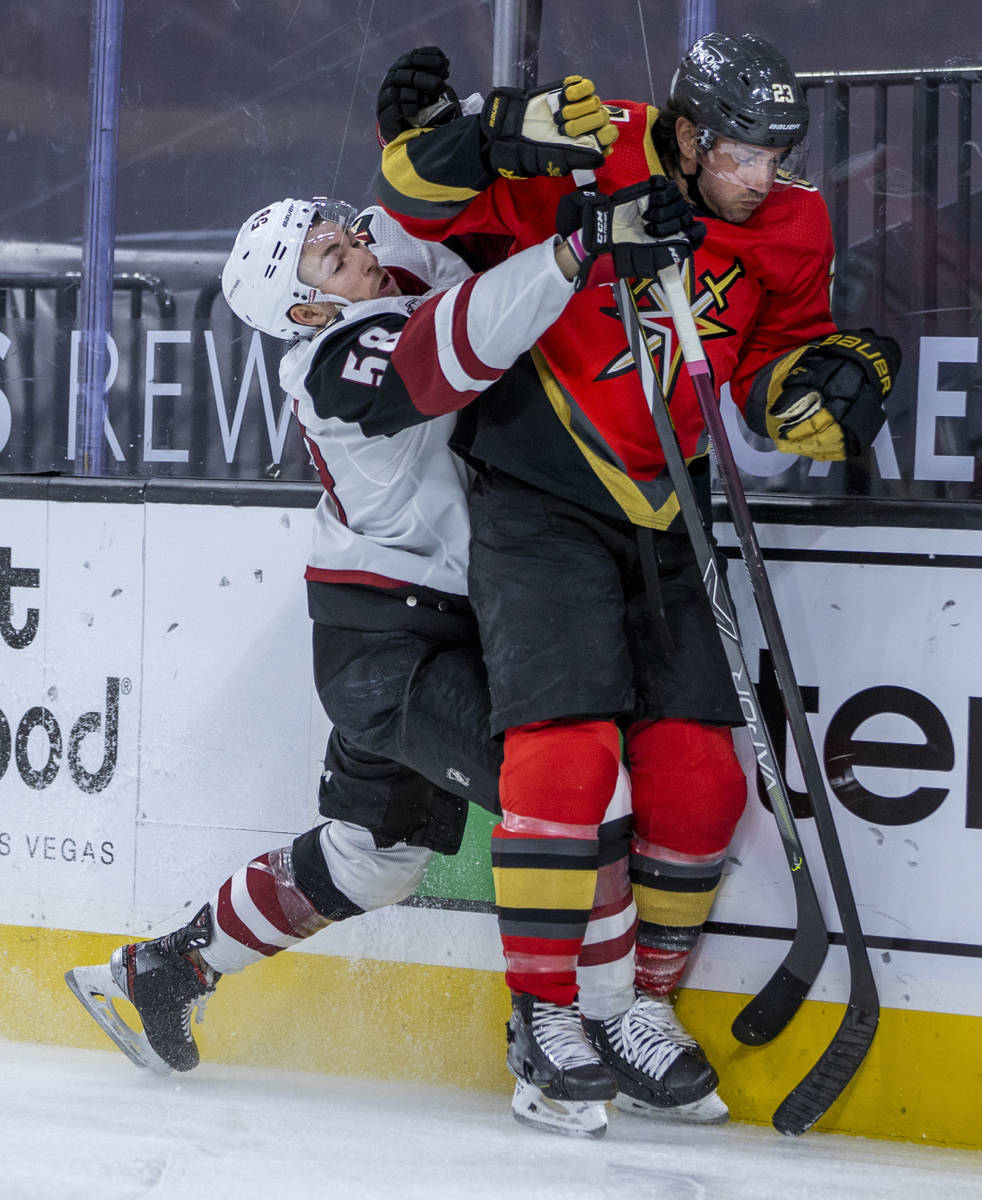Arizona Coyotes left wing Michael Bunting (58) battles with Golden Knights defenseman Alec Mart ...