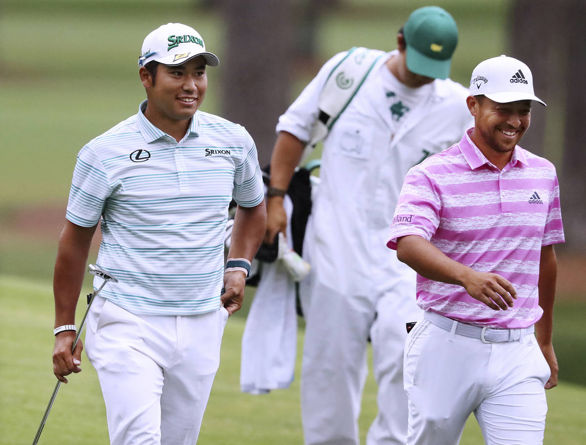 Hideki Matsuyama, left, and Xander Schauffele smile after they both made eagle putts on the 15t ...