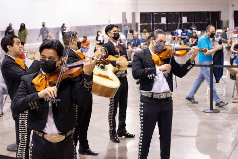 Mariachi Nuestras Raices performs to a room of people waiting in line for COVID-19 vaccines or ...