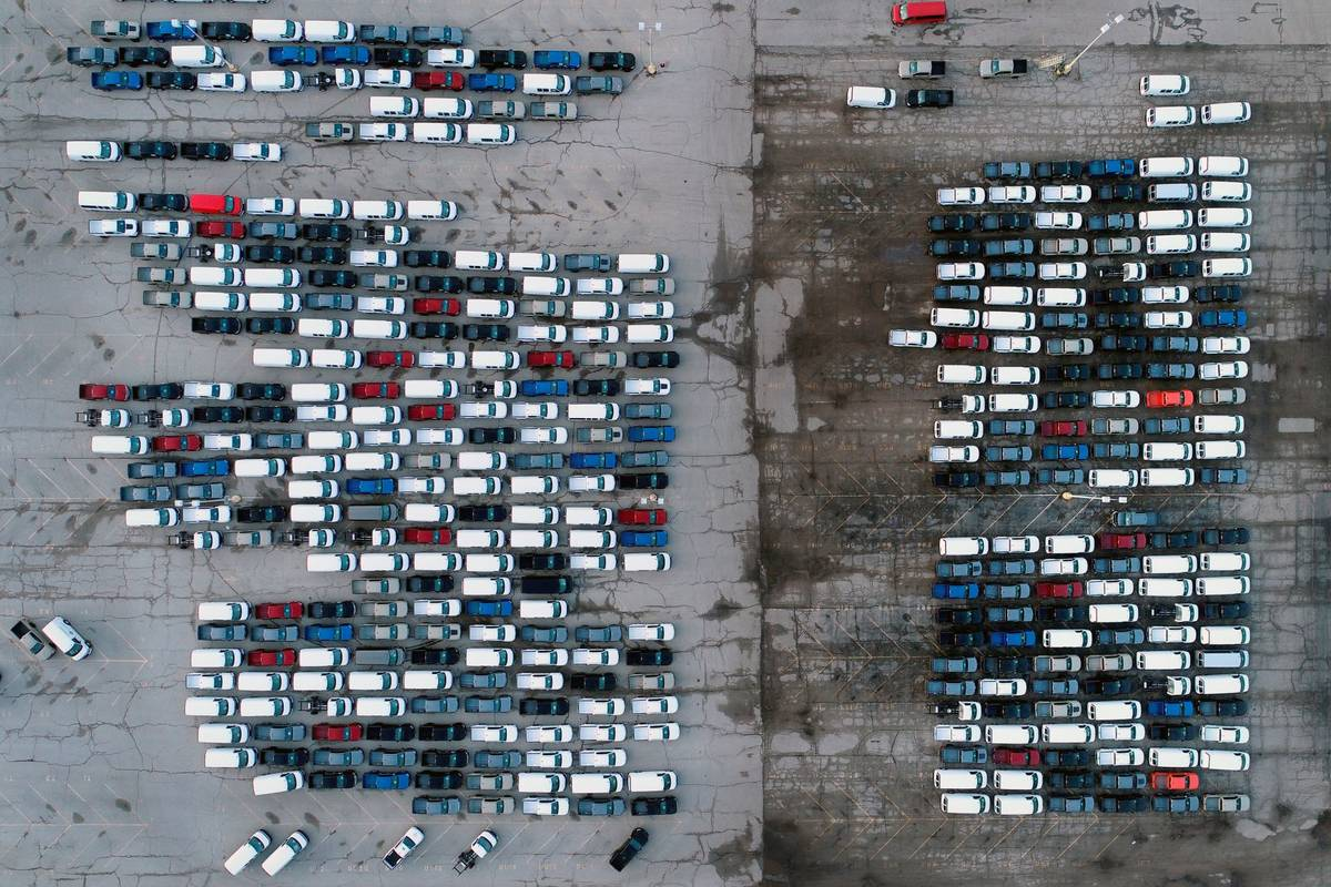 Mid-sized pickup trucks and full-size vans are seen in a parking lot outside a General Motors a ...