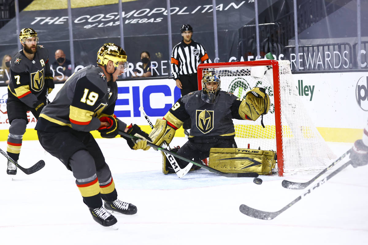 Golden Knights goaltender Marc-Andre Fleury (29) and forward Reilly Smith (19) defend the net a ...