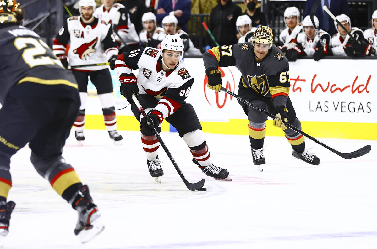 Arizona Coyotes' Michael Bunting (58) skates with the puck under pressure from Golden Knights' ...