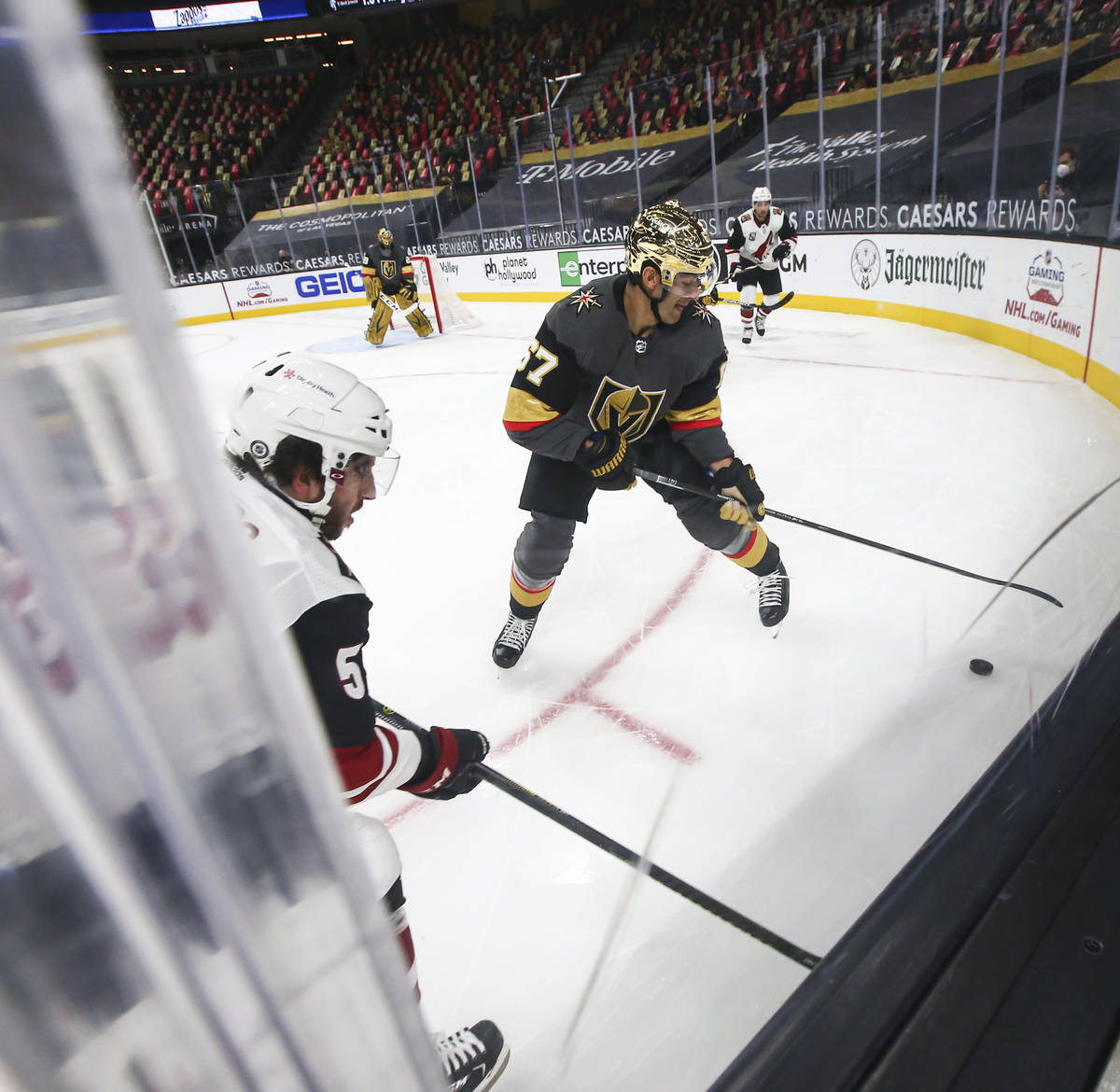 Golden Knights' Max Pacioretty (67) moves the puck under pressure from Arizona Coyotes' Jason D ...