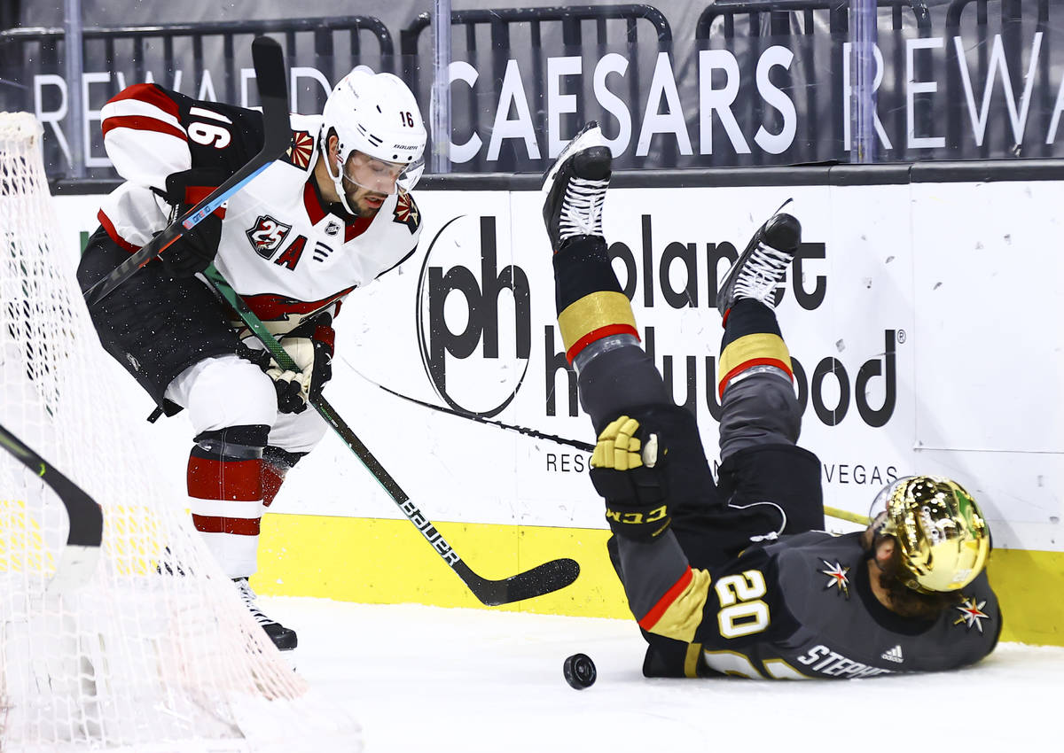 Golden Knights' Chandler Stephenson (20) gets tripped up as Arizona Coyotes' Derick Brassard (1 ...