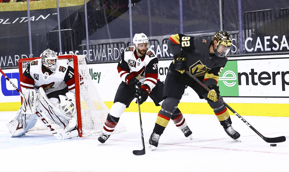 Golden Knights' Tomas Nosek (92) skates with the puck under pressure from Arizona Coyotes' Alex ...