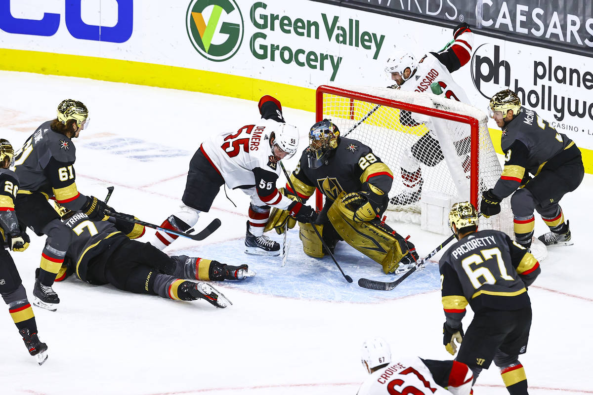 Golden Knights goaltender Marc-Andre Fleury (29) defends the net in front of Arizona Coyotes' J ...