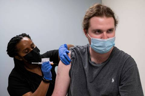 Cole Smith receives a Moderna variant vaccine shot from clinical research nurse Tigisty Girmay ...
