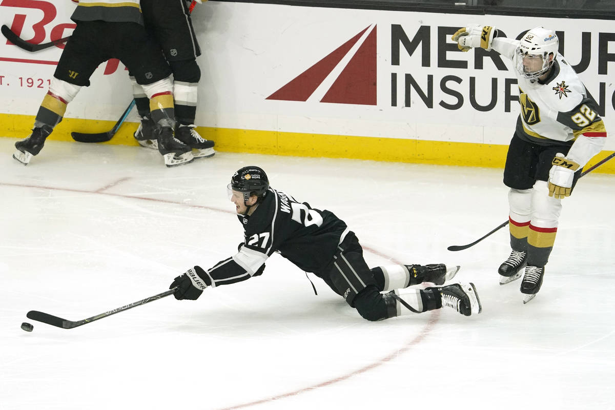 Los Angeles Kings left wing Austin Wagner, left, falls as he passes the puck while under pressu ...