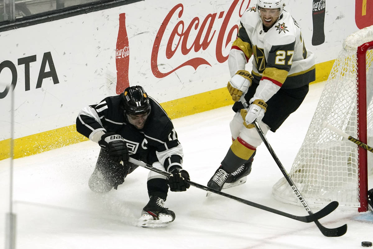 Los Angeles Kings center Anze Kopitar, left, falls as he moves the puck while under pressure fr ...