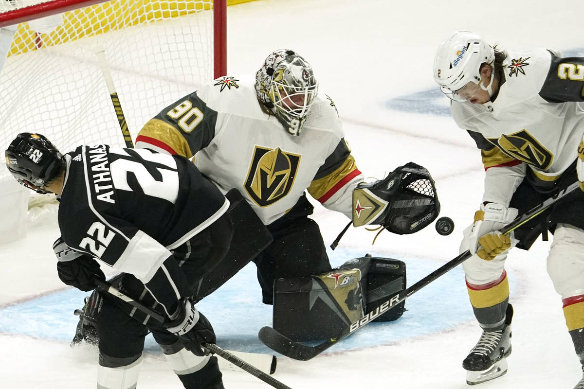Los Angeles Kings left wing Andreas Athanasiou, left, tries to get a shot past Vegas Golden Kni ...