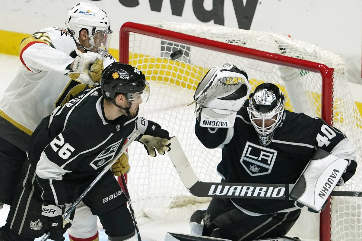 Los Angeles Kings goaltender Calvin Petersen, right, deflects a shot as Vegas Golden Knights le ...