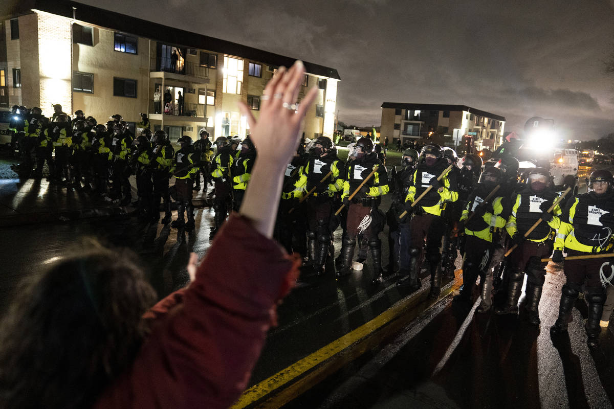 A demonstrator raises their hand while facing off against a perimeter of police as they defy an ...