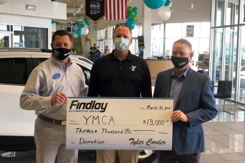 Mike Lubbe, center, president/CEO of YMCA Southern Nevada, accepts a donation check from Doug F ...