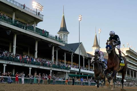 Jockey John Velazquez riding Authentic, right, crosses the finish line to win the 146th running ...