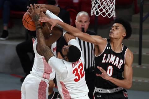 Lamar center David Muoka (0), Houston forward Reggie Chaney (32), and guard Tramon Mark, left, ...