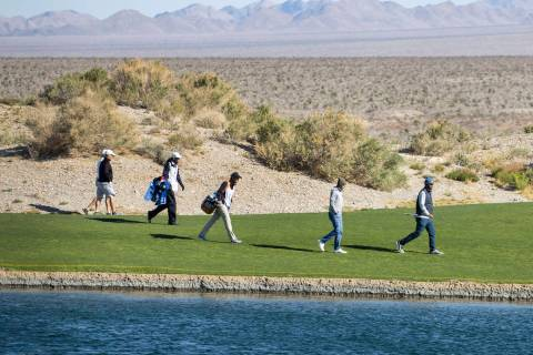 Triple-A golfers and their caddies walk past the pond during the first round of the MGM Champio ...