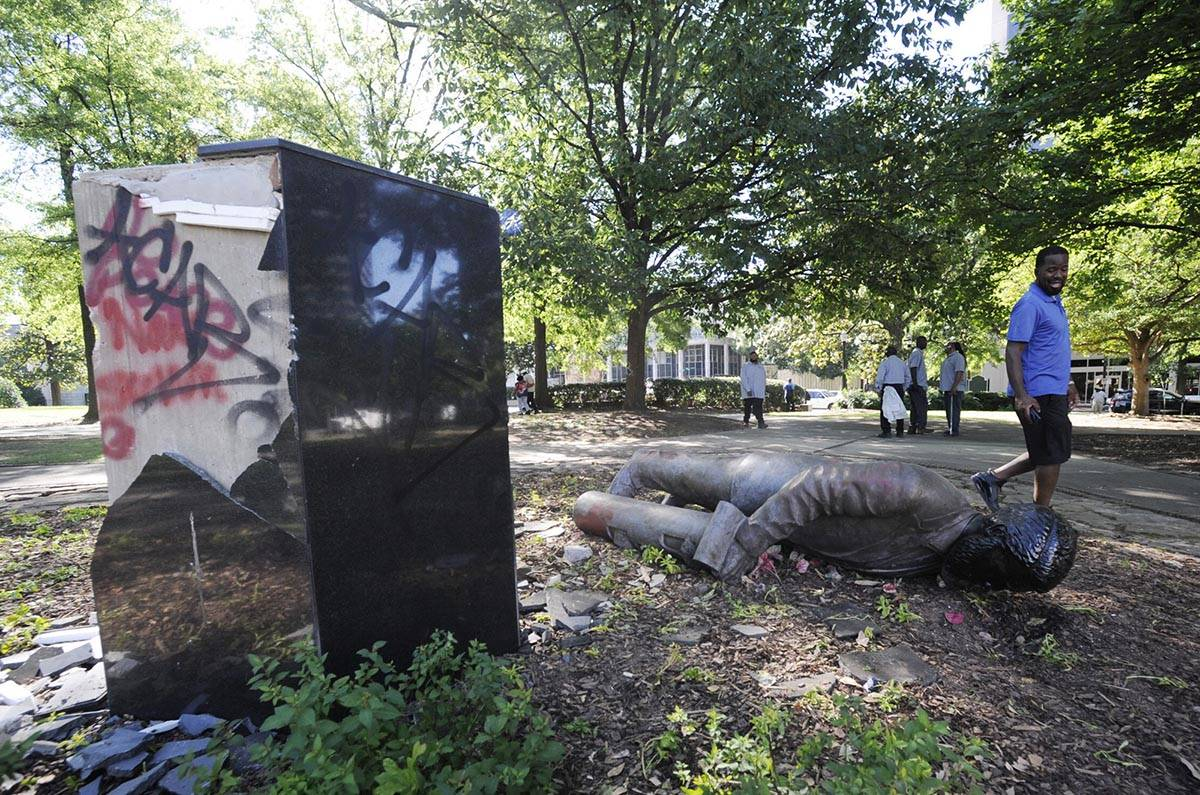 In this June 1, 2020, file photo, an unidentified man walks past a toppled statue of Charles Li ...