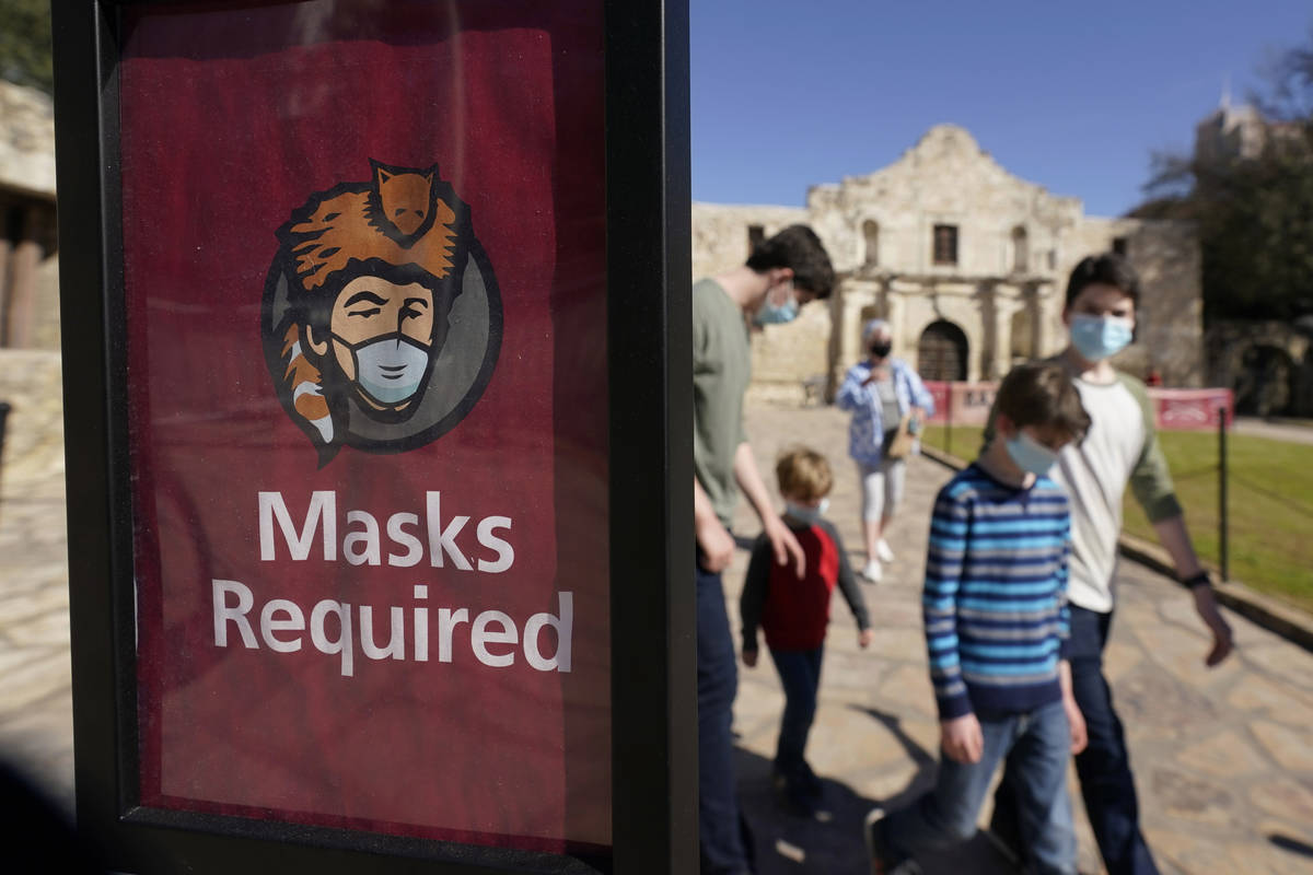 Visitors wearing face masks leave the Alamo, Wednesday, March 3, 2021, in San Antonio. Texas Go ...
