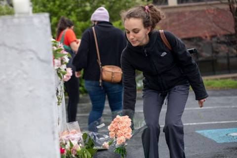 A woman places flowers near a makeshift memorial outside of the Gold Spa in Atlanta, Wednesday, ...