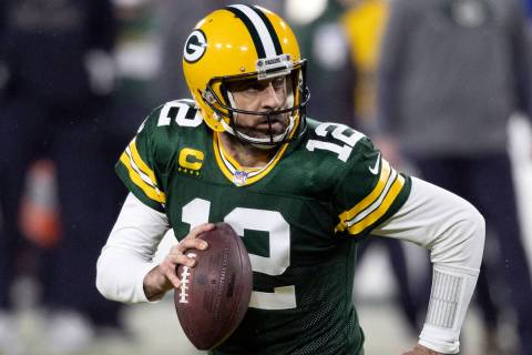 FILE - In this Jan. 16, 2021, file photo, Green Bay Packers quarterback Aaron Rodgers (12) runs ...