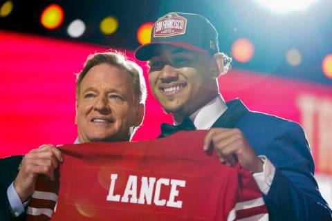 North Dakota State quarterback Trey Lance, right, holds a jersey with NFL Commissioner Roger Go ...
