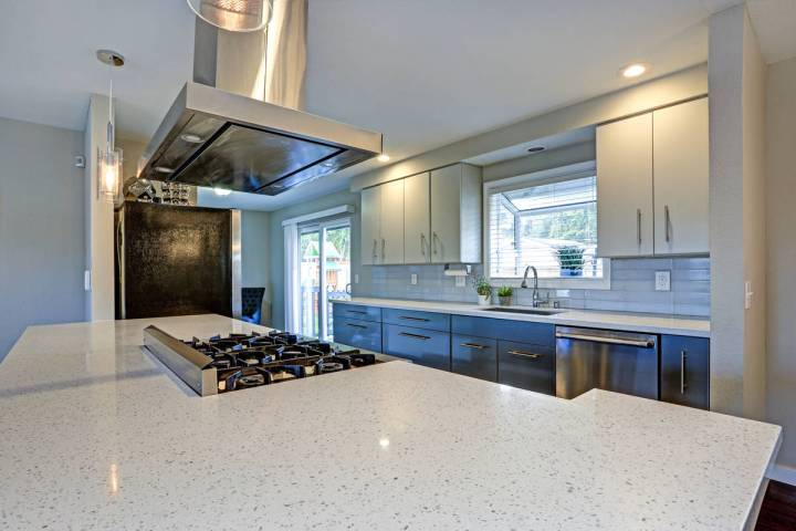 This stylish kitchen has been updated with quartz countertops and stainless steel appliances. ( ...