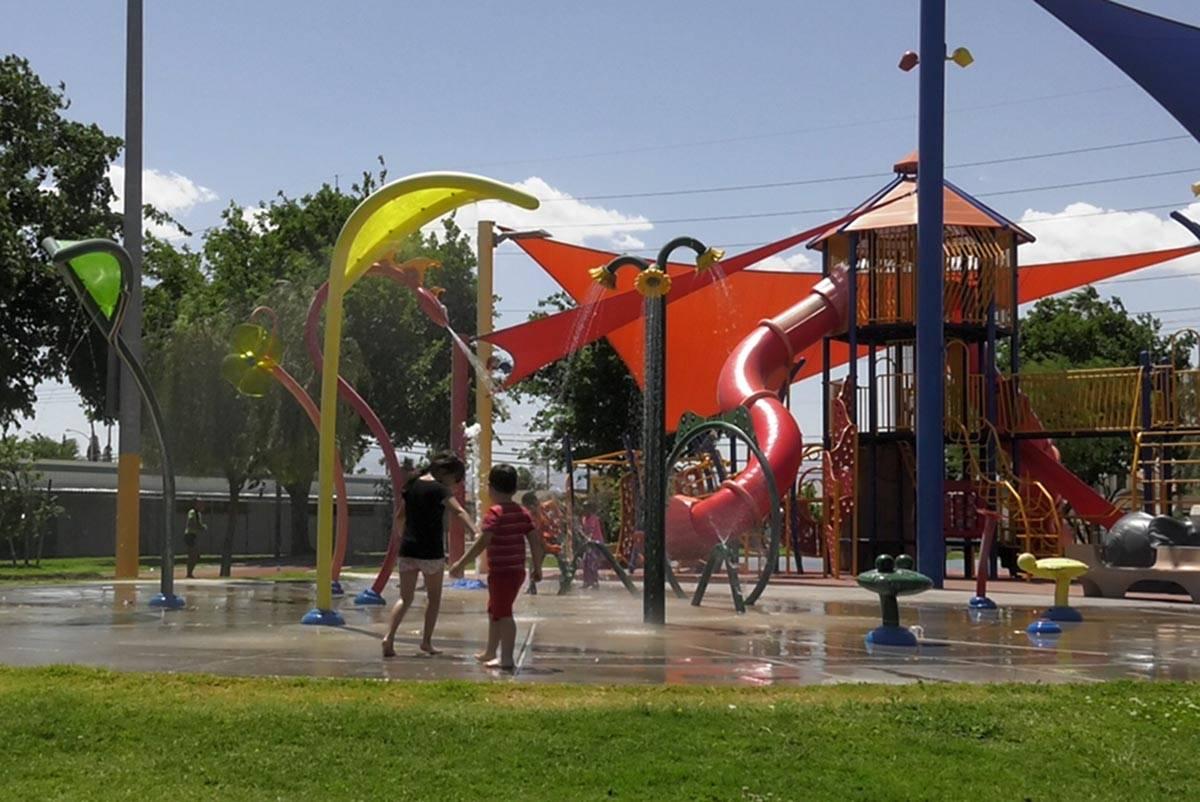 Children play at the splash pad at Kianga Isoke Palacio Park on Sunday, May 2, 2021. (Elliot Ba ...