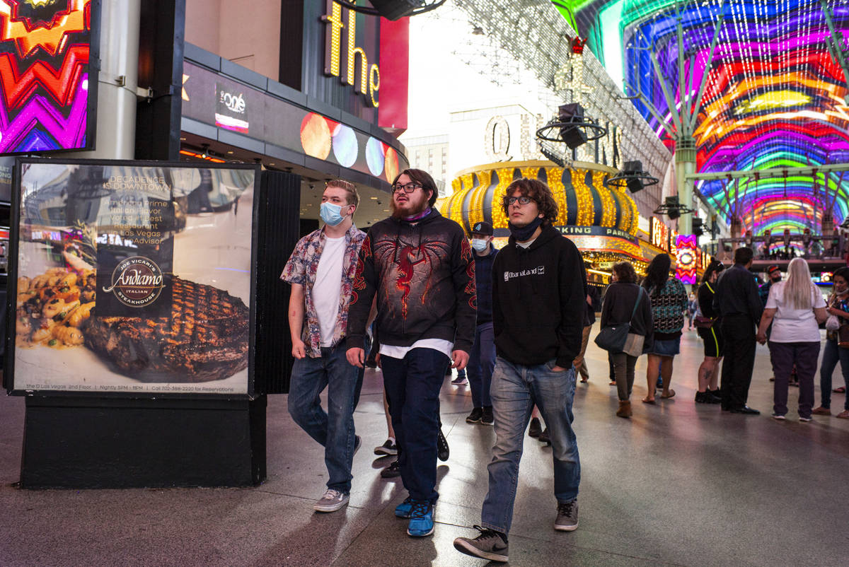 People, some wearing masks and others not, walk around the Fremont Street Experience in downtow ...
