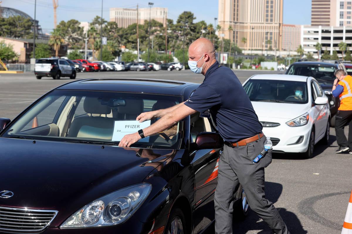 Travis Haldeman, a Clark County Fire Department engineer, marks cars during a drive-thru COVID- ...