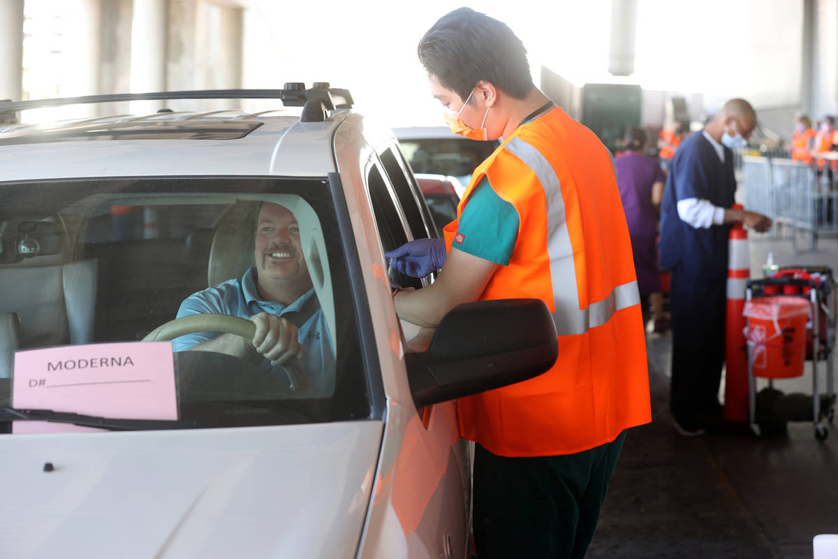 David Butler of Las Vegas gets his shot from Leo Chen during a drive-thru COVID-19 vaccine clin ...