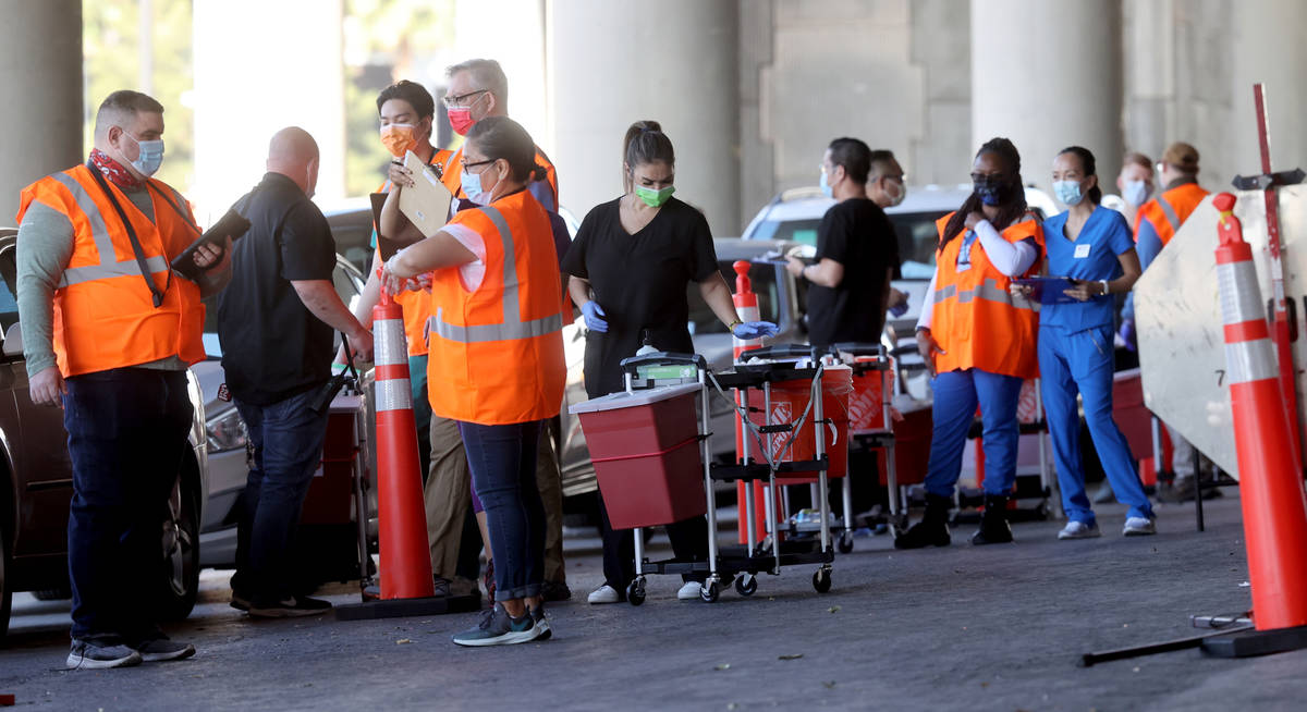 Workers prepare during a drive-thru COVID-19 vaccine clinic in the Bronze Lot at the Las Vegas ...