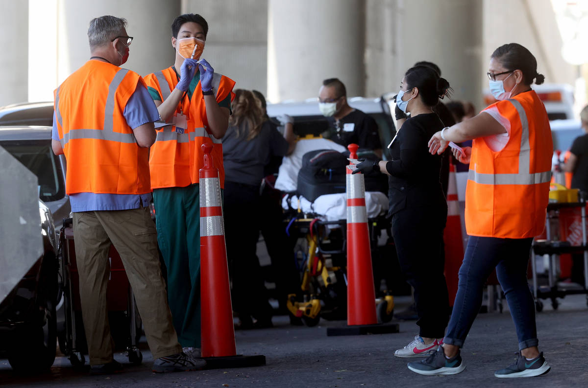 Workers, including Leo Chen, second from left, prepare to give shots during a drive-thru COVID- ...