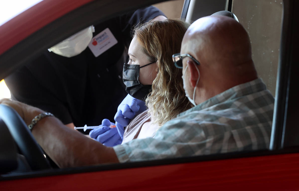 Cydney Rocheleau of Pahrump gets her shot as her father Peter Zurzolo looks on during a drive-t ...