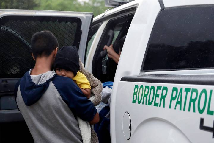 In this March 14, 2019, file photo, families who crossed the nearby U.S.-Mexico border near McA ...