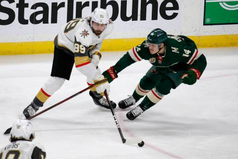 Vegas Golden Knights right wing Alex Tuch (89) controls the puck as Minnesota Wild center Joel ...
